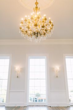 stunning gold + crystal chandelier along with floor to ceiling windows | the gadsden house | photo by catherine ann photography | king street hospitality group
