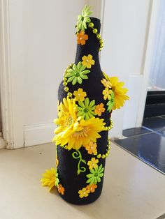 Wrapped the bottle with 12-ply black yarn. Attached flowers, beads and plastic vines with hot glue.   Will make a pretty little centre piece with some fake flowers inserted into the bottle.