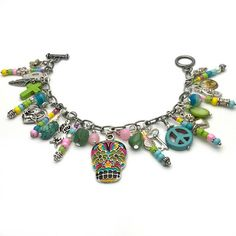 A spectacular sugar skull charm bracelet, packed with an eclectic mix of metal charms such as a hand painted sugar skulls, cherubs, feather, and flowers. And thats not all - there is a skeleton, an apple green stone cross, a magnesite peace symbol, a delicate key, a flower topped heart and a lime green mother of pearl discs. This feast of charms is interspersed with handcrafted seed bead dangles in fresh pinks, cool blues, vivid green and bright yellow as well as freshwater pearls. Length…