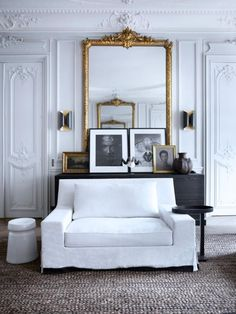 19th century flat in Paris, tall white rooms with architectural detailing painted white, large scale gilt frame mirror
