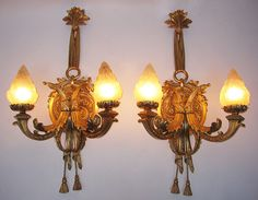 A Fine and Impressive Pair of French 19th/20th Century Louis XVI Style Gilt-Bronze Two-Light Wall Sconces, each lumière with a circular foliate backplate suspended by a ribbon tied ornament issuing two arm form cornucopias holding frosted glass flame shades ending with tassel pendants below. Circa: Paris, 1900