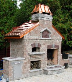 The ultimate outside patio cooking complex consisting of brick pizza oven, open fireplace, cold smoker, and charcoal BBQ