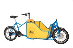 BOX BIKE: Made by hand in Santa Cruz, California. Two-wheeler with room for two kids. Fitted with electrical assist only, no throttle mode. Developed through crowdfunding, the Box Bike Collective aims at a car-free transportation future.
