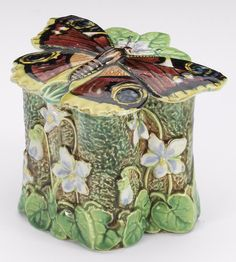 George Jones, majolica butterfly box and cover, dated 1874, The cover shaped as a butterfly, resting on a box moulded with white and blue violets set against a mottled green ground, the interior of the box coloured turquoise with a yellow rim, 9.6cm wide, moulded registration lozenge for 1874