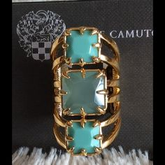 Vince Camuto Turquoise Stacked Triple Stone Ring Better together. This trio features a turquoise centered stone. Faceted squares on a gold band offers a sleek look. Oxidized gold; Glass Vince Camuto Jewelry Rings