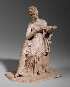 Jeune femme assise sur un rocher et jouant du luth. 1er 1/4 du 3e siècle av J.-C. Lieu de découverte : Tanagra (site) (origine). Paris, musée du Louvre