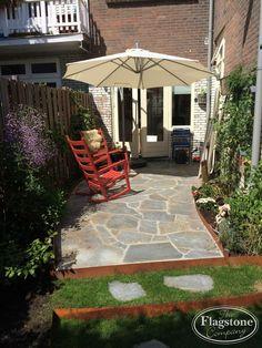 Flagstones vast gelegd in de achtertuin en losse stapstenen.
