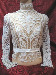Hand-assembled Victorian Battenberg tape lace blouse with an elegant pattern of scroll-work including fronds with scrolled tips and stylized flowers. The large-scale pattern is very rhythmic and the tailoring smart and crisp with a cotton waistband, elegantly shaped sleeves and a stand-up collar. The Battenberg tapes were hand-joined with twisted-thread bars embellished with coiled rings and the blouse is in excellent uncleaned antique condition with a couple of broken bridg