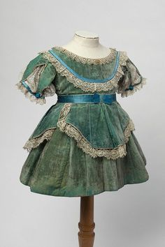 Child's short dress and basque waistband of pale sea green velvet trimmed with lace and blue ribbon (front), English, ca. 1870. The basque waistband has three tabs, one at the front and two at the back.