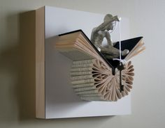 The Memory Key. The artist Daniel Lai, aka Kenjio, uses a paper folding technique to create these book sculptures. Each book sculpture features a clay figure sitting deep in thought.
