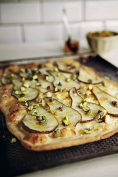 Pear, Chevre & Pistachio Pizza:   1. Preheat oven to 390F°  2. Roll out the pizza dough to a large rectangle  3. Grate 7oz of chèvre over the dough  4. Thinly slice 2-3 pears and lay on dough   5. Squeeze some lemon juice over to prevent browning  6. Bake for 15-20 minutes  7. Sprinkle on 2 tbsp of chopped pistachios & drizzle some honey over top