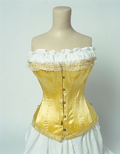 1900-05 lovely yellow sateen with Maltese lace and plush trim.  Note 3 hooks at waist.