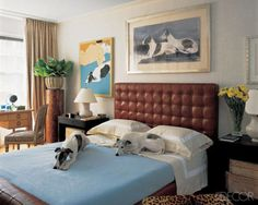 Whippets Nigel and Rupert make themselves at home on the bed of their owner, Manhattan decorator James Andrew, beneath their watercolor portrait by Peter Westcott.