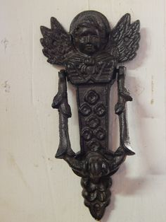 "This is Angel doorknocker. The design is either an angel or a cherub with wings. It is made of cast iron Measurements: 8 1/4"" H 4"" W"