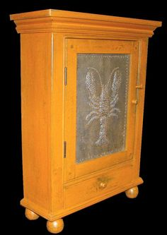 """This is a standing or hanging cupboard (feet are removable to allow use as a hanging cupboard) with a punched tin lobster.  It measures 28"""" high by 21"""" wide and is finished in a moderately distressed butterscotch over brown (it is not as orange as it appears in the photos)."""
