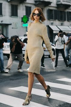 Candela Novembre struts her stuff with a wavy bob hairstyle, cat-eye sunglasses, a ribbed sweaterdress and metallic gold sandals