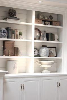 Shiplap planks painted white add texture and architectural interest to these book/collectible shelves. | Via forevercottage.blogspot.com