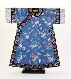 1870 Robe Culture: Chinese Medium: silk twill, floss silk This is a lady's robe, made of embroidered blue silk. It is lined with yellow silk figured with clouds. Bands of black satin adorn the collar and edges. The embroidered discs of longevity characters indicate that this was made for someone more elderly. There are also auspicious floral motifs, and the embroidered bats also extend wishes of luck and good fortune (the Chinese word for bats is a homophone of the word for luck).