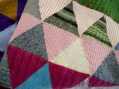 Recycled felted wool sweaters are cut apart and resewn to create this one of a kind blanket. Forget about boring, run of the mill blankets, your baby or couch deserves something much more interesting.  Rows of same color triangles are filled in with random scraps from my stash. The rows are stitched together in colors to match. With the green border, this blanket is 48 x 50, perfect size for snuggling.