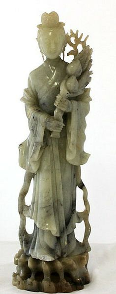A Chinese Carved Green Apple Soapstone Carving Kwan Yin modelled as a young woman , in traditional robes and hair , clasping a spray of peaches to her breast ,resting on a softstone plinth , oh 35cm h 31cm