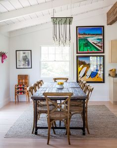 A pitched ceiling with exposed beams. Caned dining chairs paired with a wooden dining table.