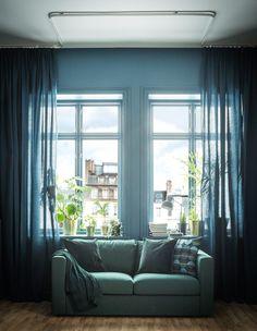 GIF montrant des rideaux bleus pleine hauteur en train d'être tirés autour d'un canapé.