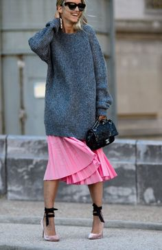 Oversized long gray sweater over pink pleated skirt.