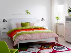 Ein Schlafzimmer mit DUKEN Bettgestell in Weiß, ÄNGSKRASSE Bettwäsche-Sets in Bunt, SELJE Ablagetischen in Weiß und kurzflorigem GULÖRT Teppich in Bunt
