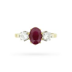A pair ofround brilliant cut diamonds sparkle alongside a 1.30 carat oval-shaped ruby in this vintage mid-century 18 carat yellow and white gold rendition of the timeless three stone engagement ring. This circa 1950s ring was handmade in the style of its era with open back claw mountings, tapered shoulders, and ridged detailing on its …