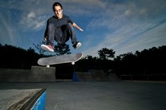 11962049 - skateboarder on a flip trick at the local skatepark.
