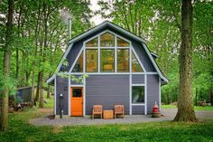Originally used as a garage with two horse stalls, the existing stick framed structure provided a loft with ideal space and orientation for a secluded studio. A two-story garage converted into a couple's retreat in Garrison, New York by Hudson Design. Gambrel Barn, Gambrel Roof, Grey House White Trim, Gray Trim, Barndominium Pictures, Two Story Garage, Building A Pole Barn, Building Homes, Barn House Kits
