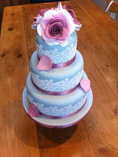 Blue three tier wedding cake with edible lace finished with dusky pink hand made roses & petals x