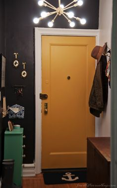yellow door in foyer of a Brooklyn apartment in NYC.  Color is Bryant Gold by Benjamin Moore that is a strong contrast to the black walls (Black Jack by Benjamin Moore)
