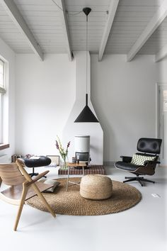 Bright, white living space with open beams and high ceilings | home to Dutch designer Christien Starkenberg | black Eames lounger | natural textiles mixed with a white interior | Kitchen of the Week: The Curtained Kitchen, Dutch Modern Edition - Remodelista