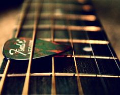 "Nice photo of guitar fretboard holding a green pink camouflage style Fender guitar pick the ""cool"" way. In reality, if you store your pick between strings this low on your fretboard, it's gonna slide out when you lift your guitar up... probably right into sound hole if it's an acoustic guitar! (USE A PENCIL ERASER TO FIRMLY HOLD PICK, THEN TURN GUITAR UPSIDE DOWN TO SHAKE OUT) -DdO:) http://www.pinterest.com/DianaDeeOsborne/instruments-for-joy - Photo credit: alibubba - Pin via Miranda…"