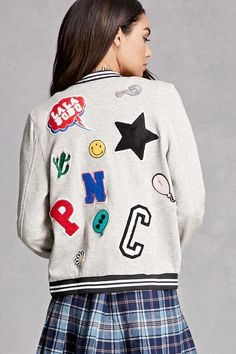 A heathered knit varsity jacket featuring various patches on the back including a star, speech bubble, happy face, letters, exclamation point, a cactus, and a happy face, as well as a zip-up front, contrast stripes on the ribbed trim, two front slanted pockets, a French terry lining, and long sleeves. This is an independent brand and not a Forever 21 branded item.