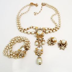 "This vintage signed Miriam Haskell set features bezel cut clear glass, faux pearls and clear rhinestones in a gold-tone setting. The necklace has an inside strand measurement of 20 ¼"" with a hook closure and the pendant is 5"" x 1 ½"". The clip earrings are 1 ¼"" x 1"" and the 4-strand bracelet is 7"" x 1 ½"". In excellent condition, this set is signed Miriam Haskell. From www.1stdibs.com"