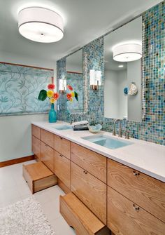 "This bathroom features a blue ""sea like"" backsplash and hidden step stools for easy, kid-friendly accessibility."