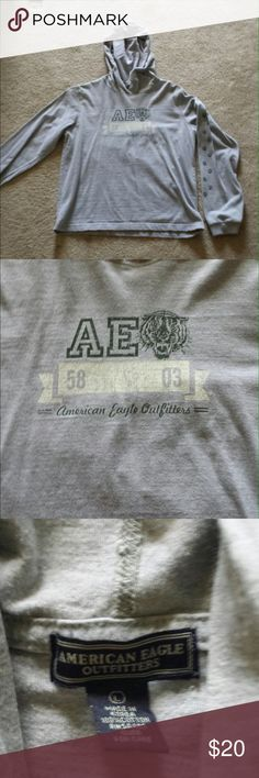 American Eagle long sleeved t-shirt with hood. Gray long sleeved t-shirt. Minimal signs of wear. Light weight. Has hood. Paw prints go up left arm. No print on the right sleeve. American Eagle Outfitters Tops