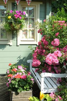Oh, I LOVE this...the color of the house, the design of the trim, the bunting, hanging basket and the ROSES!