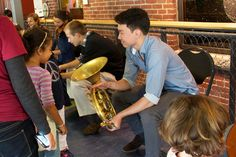Ray Seong Jin Han shares his horn with a young guest