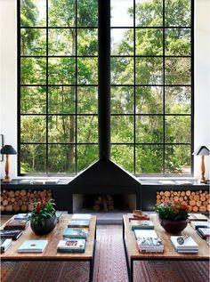 La symétrie parfaite de ce salon est strictement respectée. Le conduit de la cheminée sépare la haute verrière en deux parties égales tandis que les deux tables basses accueillent les mêmes dispositions de plantes et de magazines.