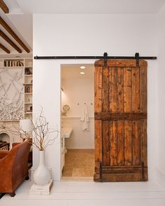 Modern eclectic bathroom with a lovely barn door [Design: The Brooklyn Home Company / Emily Gilbert Photography]