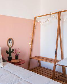 Arara de madeira serve como armário nesse quarto jovem.