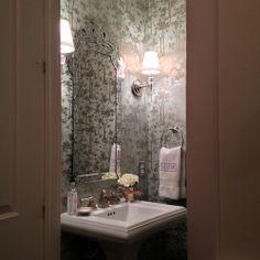 glam powder bath in Houston, Texas Osborne & Little wallpaper, crystal sphere sconces, Venetian mirror
