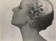 Nautilus-shaped diamond ear clips by Rene Boivin (curled hair style by Antoine), 1934. Photo by George Hoyningen-Huene.