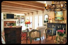 The beams, sideboard, copious light from French doors, pretty green chairs, lighting fixture. Making a home over time is so attractive.