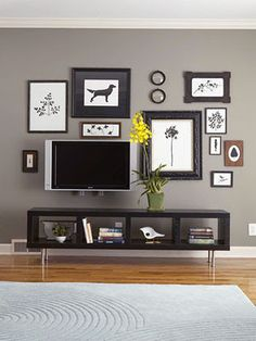 I am trying to decide how to decorate the blank wall around my TV. I like how all the black and white camouflages the TV.