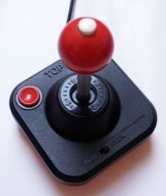 Wico Command Control Famous Red Ball Joystick :-: The famous older brother of the Baseball Bat Joystick, this controller is just a thing of beauty. & would look amazing in a display case. Built to be practically indestructible, the joystick was very much built to emulate arcade style joysticks of the age and intended for the wanton destruction of all video games. A very solid and base heavy device, a user could select via a slide switch whether to fire from the base or the stick.
