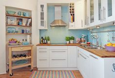 A nicely organized, cute, little kitchen. I love how the blue backsplash lightens everything up, and the nook is a great place for cookbooks and to stash the island when not using it.